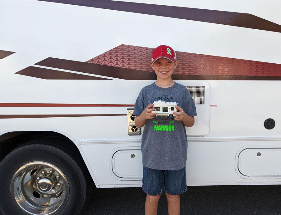 Ryder Klop, 10, holding a Lego RV